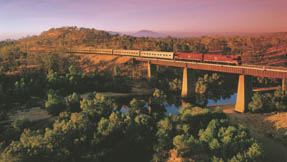 The Ghan crossing a bridge at sunset