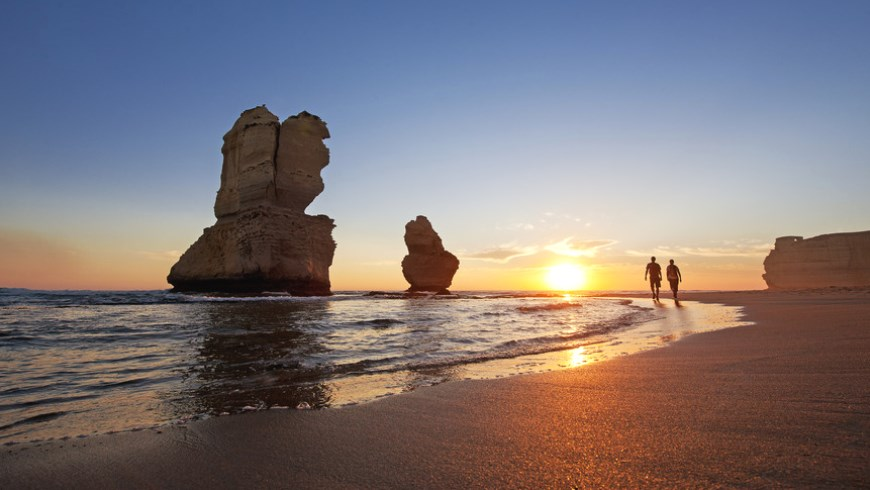 A couple walk beside the Twelve Apostles at sunset