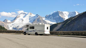 An RV sits by the side of the ride in front of the Canadian Rockies