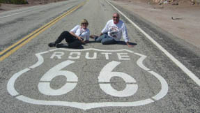 Some excited people sitting on the road outside route 66 markings